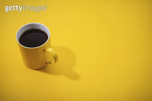 High angle view of yellow coffee mug on yellow background. - gettyimageskorea