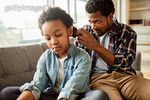 Cropped shot of a carefree little girl browsing on a digital tablet while her father fixes her hair at home during the day - gettyimageskorea