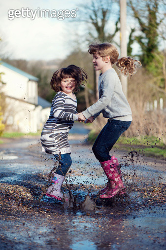Sisters Jumping In A Muddy Puddle - gettyimageskorea
