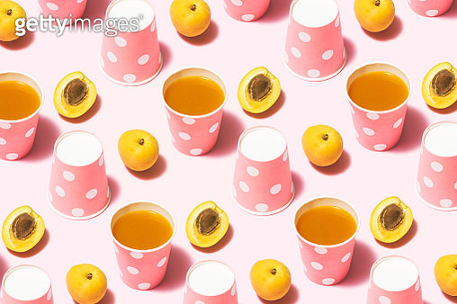 Peach juice and pink polka dot paper cups flat lay on pink background - gettyimageskorea