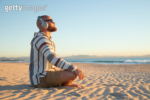 Man with headphones sitting at the beach - gettyimageskorea