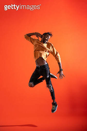 Young man jumping and dancing in front of orange wall - gettyimageskorea