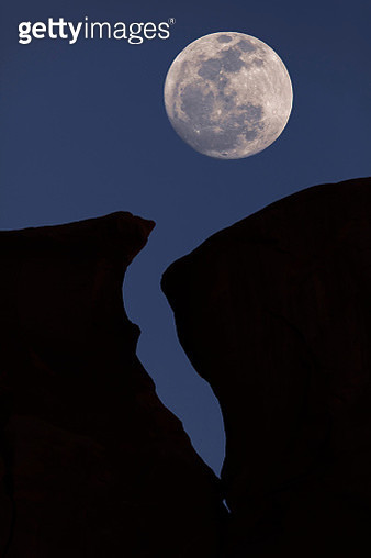 Silhouetted crack in mesa with full moon, near Monument Valley, Arizona, USA - gettyimageskorea