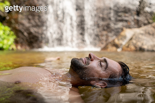 Happy man relaxing and floating in the water - gettyimageskorea
