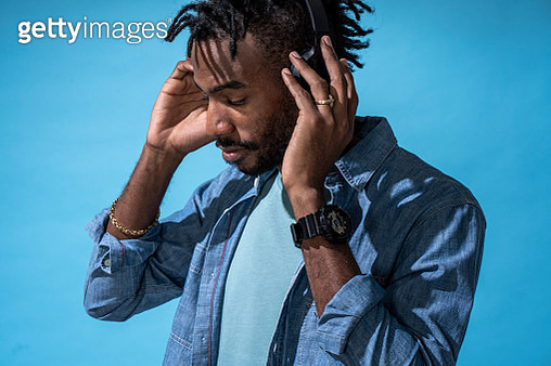 Portrait of stylish young man listening to music with headphones - gettyimageskorea