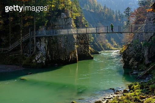 Austria, Tyrol, hiker on suspension bridge looking at Tiroler Ache in autumn - gettyimageskorea
