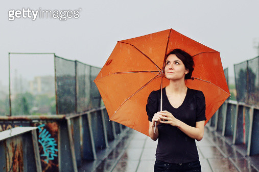 young woman with orange umbrella in the rain - gettyimageskorea