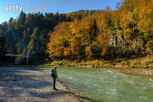 Germany, Bavaria, Upper Bavaria, Chiemgau, near Schleching, hiker standing at Tiroler Ache riverside in autumn - gettyimageskorea
