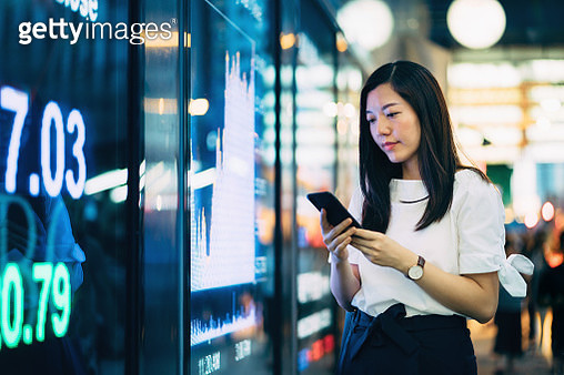Confidence young Asian businesswoman checking financial trading data on smartphone by the stock exchange market display screen board in downtown financial district - gettyimageskorea
