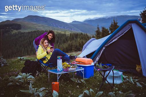Women using smart phone on camping - gettyimageskorea