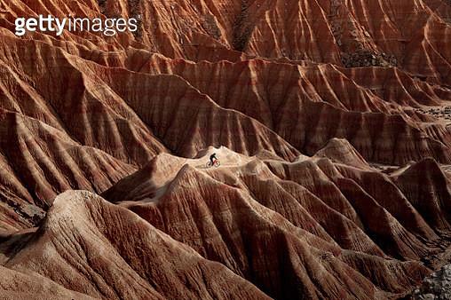Biker riding the rugged sandstone formations in the desert landscape of Bardenas Reales badlands in Spain. Montando en bicicleta en el paisaje desertico de las Bardenas Reales en el norte de España con formaciones de tierra. - gettyimageskorea