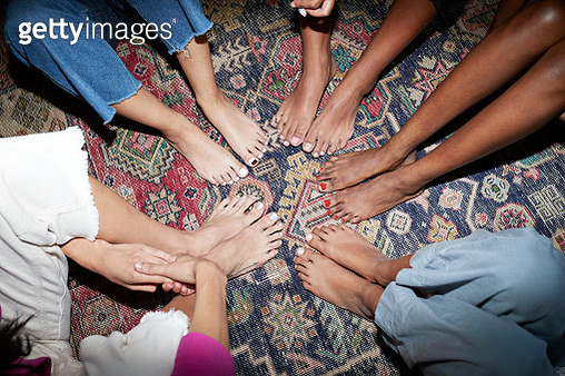 High angle view of women with painted toenails sitting in circle on carpet - gettyimageskorea