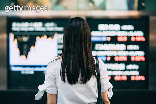 Rear view of businesswoman looking at stock exchange market display screen board in downtown financial district - gettyimageskorea