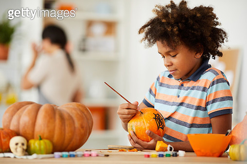 Smiling creative child with Afro hairstyle leaning on counter with gouaches and making design on pumpkin - gettyimageskorea
