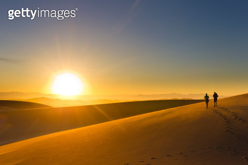 Hispanic couple walking on sand dune at sunset - gettyimageskorea