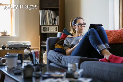 Woman using digital tablet on sofa - gettyimageskorea