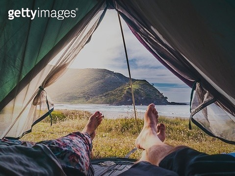 Low Section Of People Lying In Tent Against Mountain And Sea - gettyimageskorea