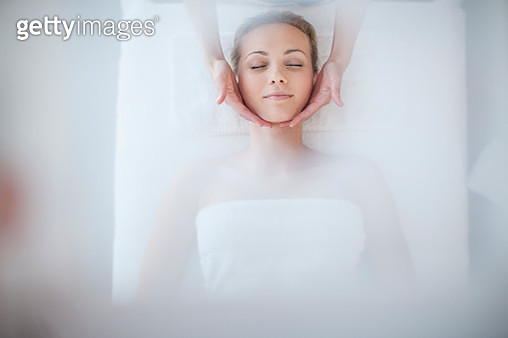 Young woman lying on massage table receiving beauty treatment - gettyimageskorea