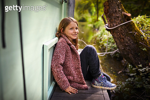 Smiling girl sitting on a houseboat - gettyimageskorea