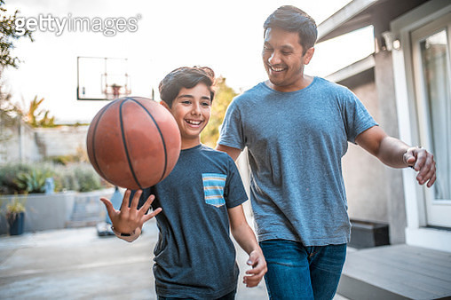 Boy spinning basketball while walking by father - gettyimageskorea