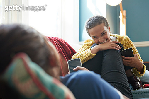 Cheerful friend listening to woman while relaxing on sofa at home - gettyimageskorea