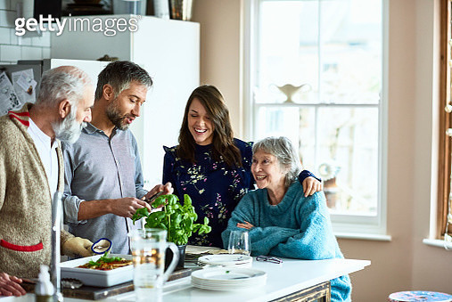 Cheerful mid adult woman with arm around her mother smiling and watching her husband prepare meal, mature father with grey hair and beard standing by kitchen island - gettyimageskorea
