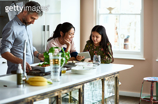 Modern family life with mature man making dinner, wife and mixed race girl using device, sitting around kitchen island, freshly home cooked meal on work surface - gettyimageskorea