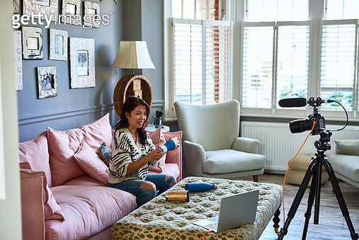 Video channel influencer making vlog at home in living room, holding reusable coffee cup, talking and comparing - gettyimageskorea