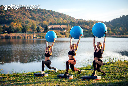 Women exercise next to the lake with ball. - gettyimageskorea