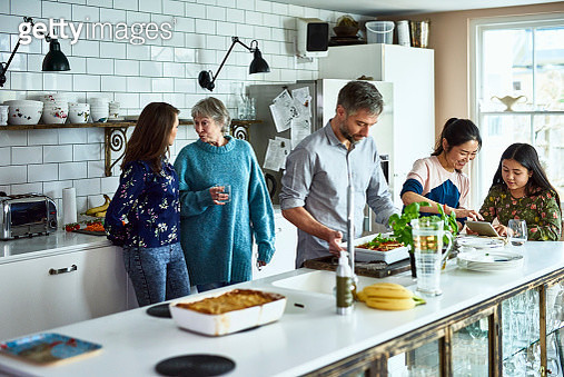 Mature man preparing home cooked dinner for his family, three generations, grandmother, adult offspring and mixed race granddaughter at home, socialising and chatting - gettyimageskorea