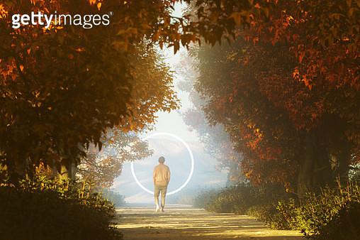 Young man walking towards mysterious portal - gettyimageskorea