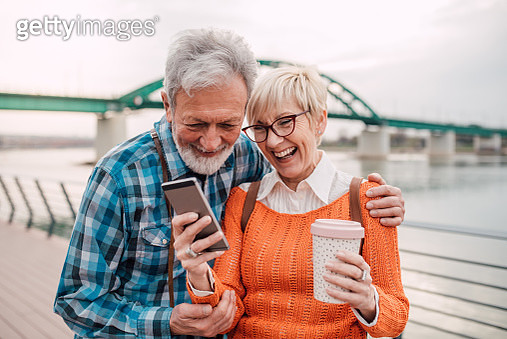 Senior couple drinking coffee and looking at phone - gettyimageskorea