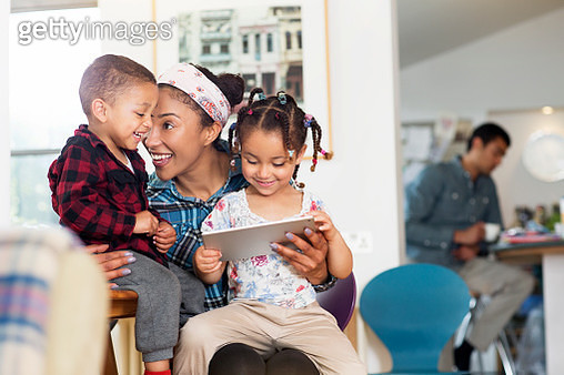 Mother, son and daughter having fun with tablet - gettyimageskorea