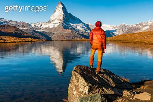 Man on the Stellisee Lake looking at Matterhorn peak. Zermatt, Switzerland. - gettyimageskorea
