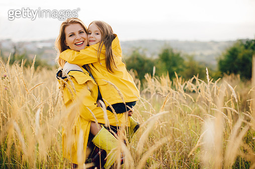 Mother with her cute daughter in meadow. - gettyimageskorea