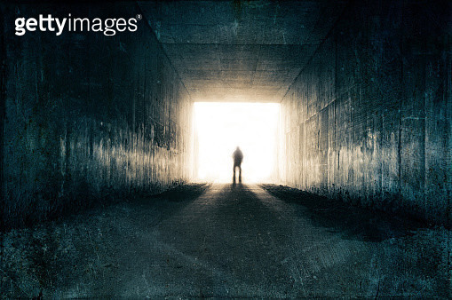 A silhouette of a blurred figure emerging from the light at the end of a dark sinister tunnel. With a grunge, vintage, grainy edit. - gettyimageskorea