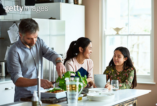 Mother and daughter chatting in kitchen as father makes dinner - gettyimageskorea
