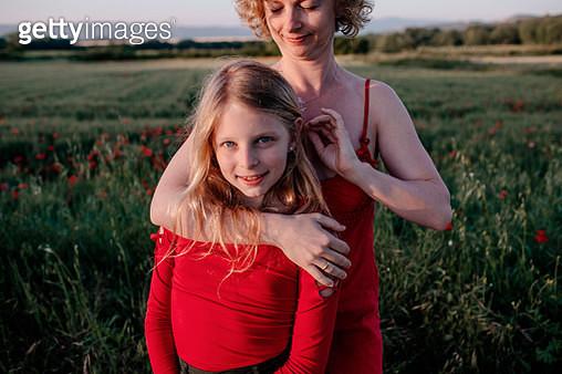 Mother stroking daughte's hair, standing in a poppy field - gettyimageskorea