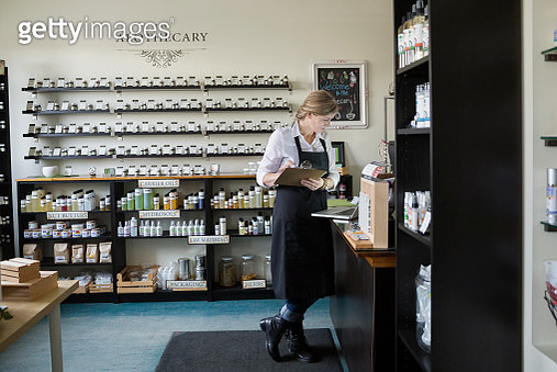 Apothecary shop owner taking inventory with clipboard - gettyimageskorea