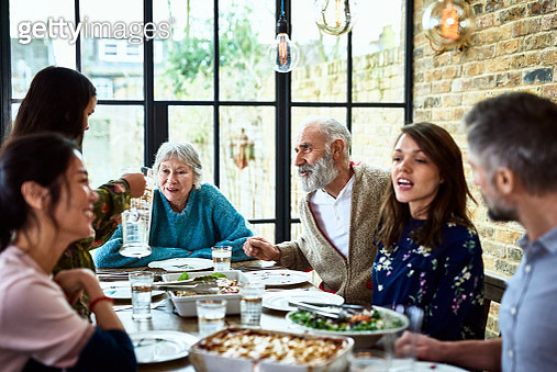 Mixed age ranges enjoying meal together in family home, pre teen girl pouring water for dinner guests, social vibrant lively family gathering - gettyimageskorea