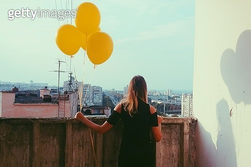 Rear View Of Woman Holding Balloons On Balcony - gettyimageskorea