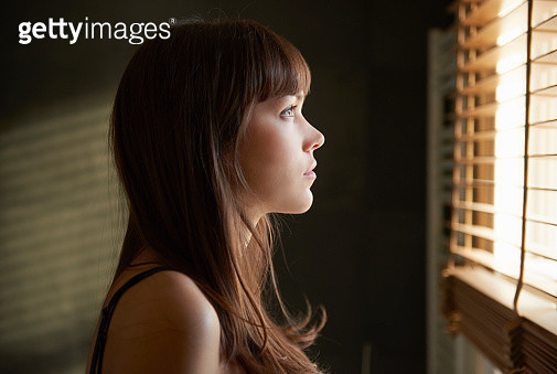 Young woman looking out of window - gettyimageskorea