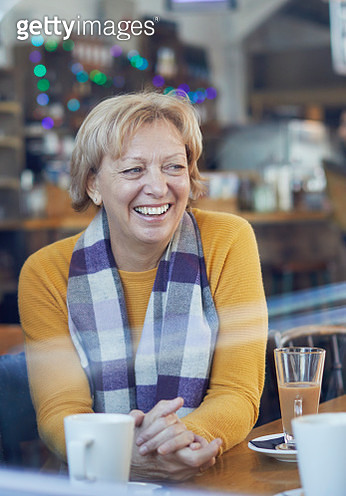 Smiling mature woman drinking coffee at cafe table - gettyimageskorea