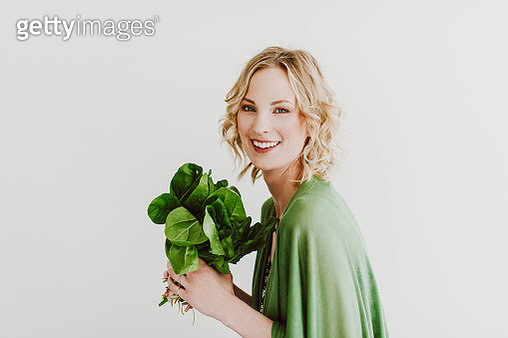 Young woman with fresh spinach - gettyimageskorea