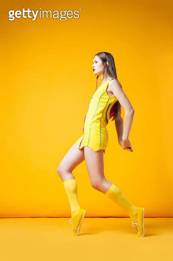 Young attractive woman wearing yellow dress with hands behind her back. Vertical studio shot. - gettyimageskorea