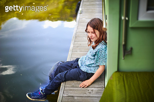 Girl sitting on a houseboat - gettyimageskorea