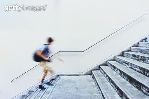 Blurred Motion Of Man Moving Up Staircase - gettyimageskorea
