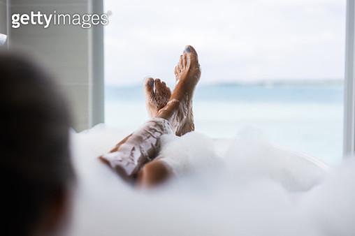Unrecognizable woman's feet in bubble bath. - gettyimageskorea
