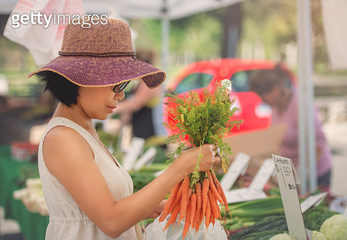 Woman Buying Carrots - gettyimageskorea