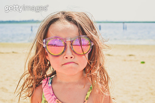 Young girl at the beach wearing sunglasses. - gettyimageskorea